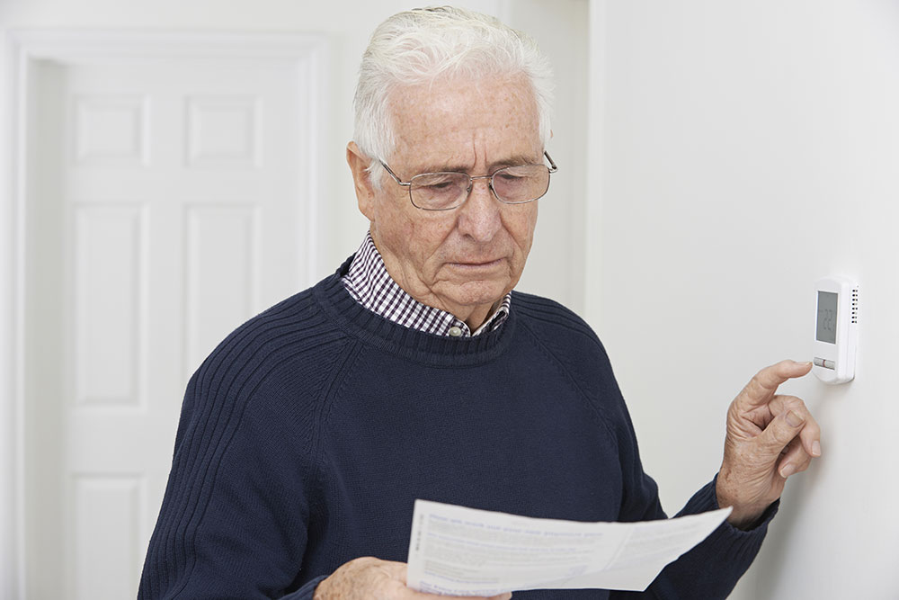Elderly man looking at an electric bill while adjusting his thermostat