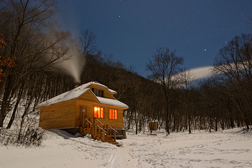 Small cabin with lights on in the dark during the winter