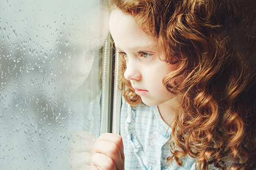 Sad redheaded little girl looking outside through a wet window