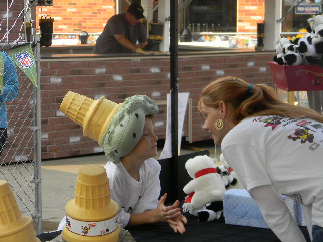 Young woman talking to a child with a ice cream cone hat on his head