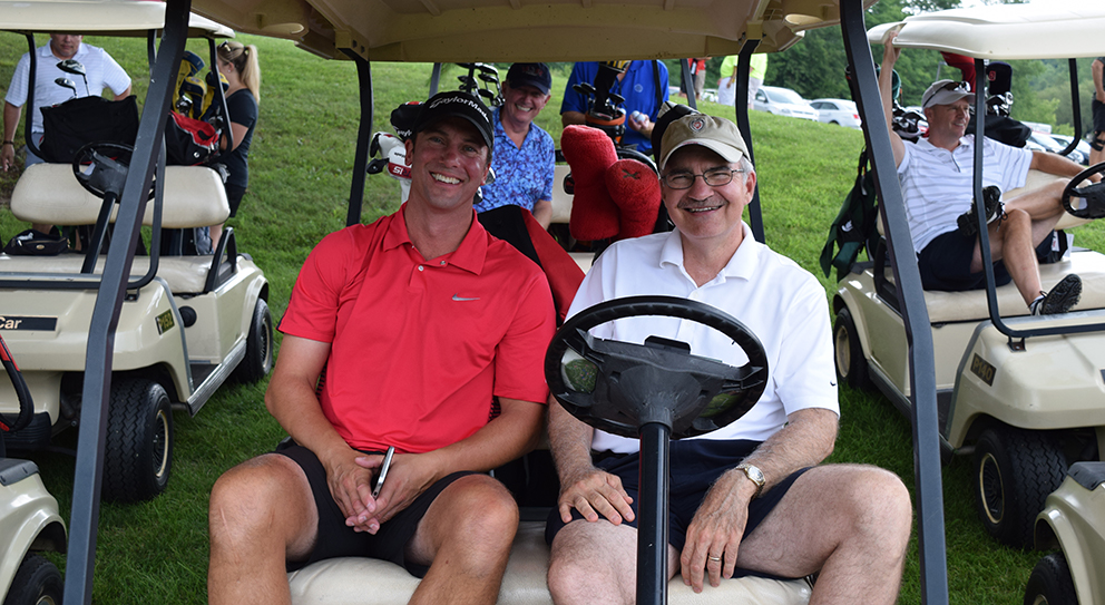 Two participants sitting in a cart at the 2016 Keep Wisconsin Warm/Cool Fund golf outing